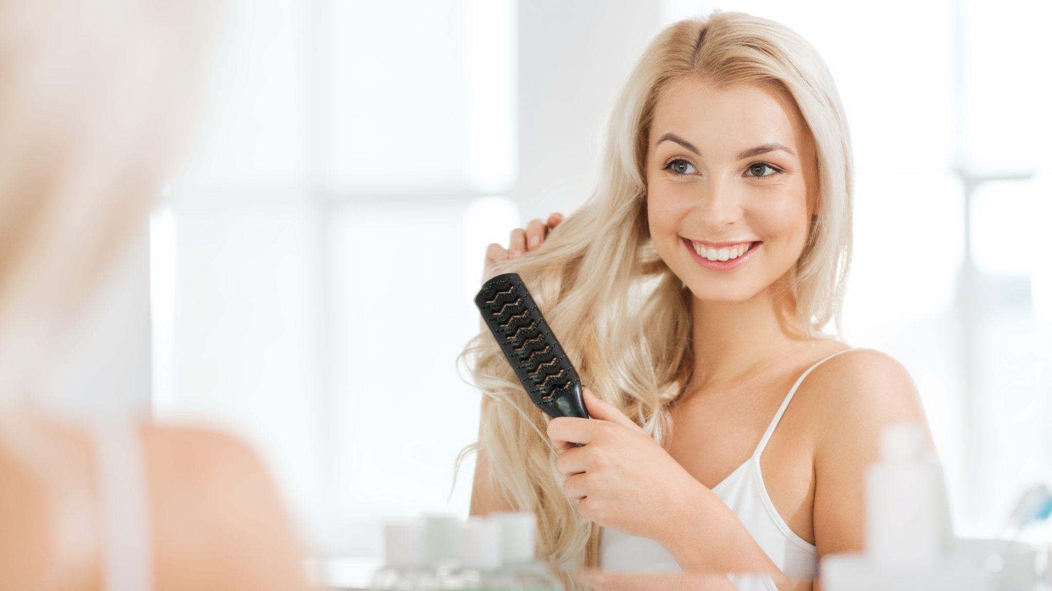 Junge Frau kämmt ihre Haare