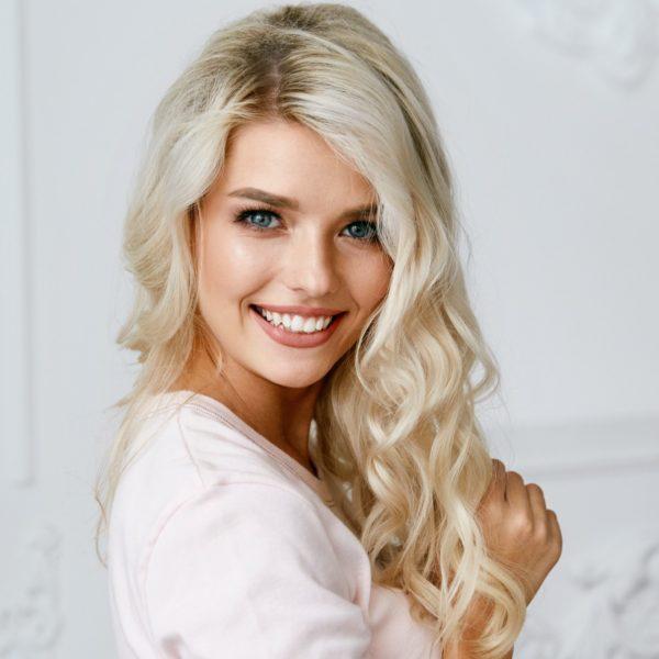 Lächelnde Blondine mit gewellten Haaren
