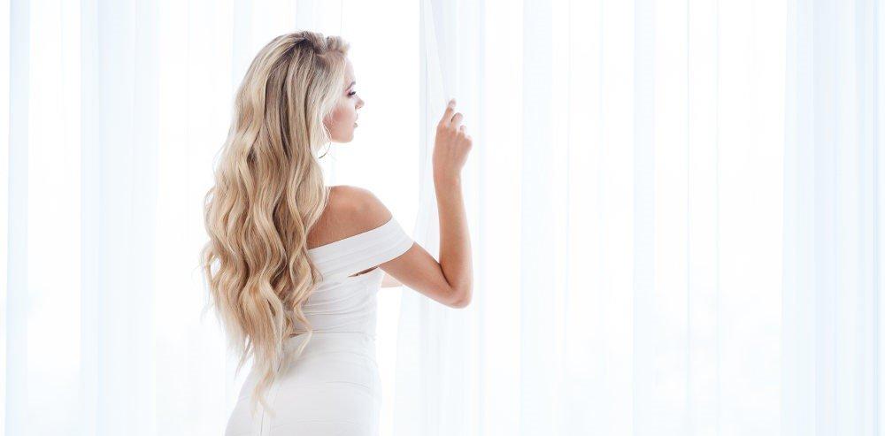 Frau mit Extensions guckt ins Fenster
